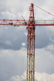 Assembling of crane on dramatic cloudy background. Dangerous height situation. Stock Images