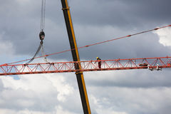 Assembling of crane on dramatic cloudy background. Height tower crane. Stock Images