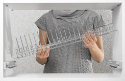 Assembling dish rack inside kitchen cupboard Stock Photos