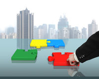 Assembling four puzzles on table. In office Stock Images