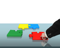 Assembling four puzzles on table Stock Photo