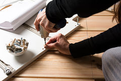 Assembling furniture from chipboard, using a cordless screwdrive. R, close up Stock Photo