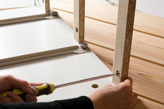 Assembling furniture from chipboard, using a cordless screwdrive Royalty Free Stock Image
