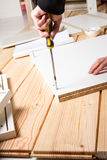 Assembling furniture from chipboard, using a cordless screwdrive. R, close up Royalty Free Stock Image