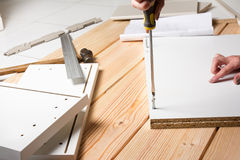 Assembling furniture from chipboard, using a cordless screwdrive Stock Photo