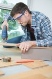 Assembling furniture from chipboard using cordless screwdriver. Assembling furniture from chipboard using a cordless screwdriver Royalty Free Stock Images