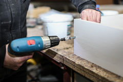 Assembling furniture from chipboard, using a cordless screwdriver, close up. Royalty Free Stock Photo