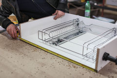 Assembling furniture from chipboard, using a cordless screwdriver, close up. Stock Photos