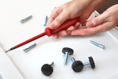 Assembling furniture, hand with screwdriver, adjustable plastic Stock Photography