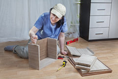 Assembling of furniture, woman mounts box of chipboard, using gl Royalty Free Stock Images