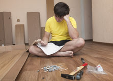 Assembling furniture. Young man puzzled about assembling flatpack closet royalty free stock photo