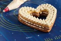 Assembling a heart-shaped cake using butter cream royalty free stock images