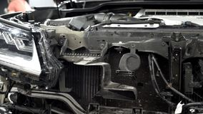 Assembling hood of car in automotive plant. Action. Close-up of details of front of car on background of mechanics in. Overalls assembled at modern enterprise royalty free stock photo