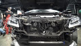 Assembling hood of car in automotive plant. Action. Close-up of details of front of car on background of mechanics in. Overalls assembled at modern enterprise royalty free stock image
