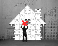 Assembling house shape puzzles on concrete wall. With doodles Royalty Free Stock Photography