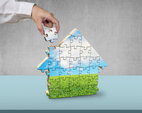 Assembling house shape puzzles. On desk Royalty Free Stock Image
