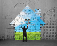 Assembling house shape puzzles on wall Stock Photos