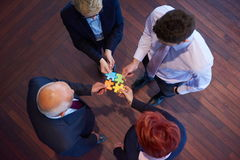 Assembling jigsaw puzzle. Business people group assembling jigsaw puzzle and represent team support and help concept, top view perspective at modern bright Royalty Free Stock Image