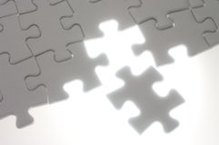 Assembling jigsaw puzzle pieces against the light. Royalty Free Stock Images