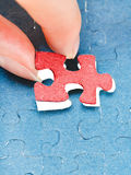 Assembling the last red piece of puzzle Stock Photos