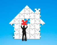 Assembling last red puzzle into house shape Royalty Free Stock Image