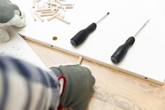 Assembling new wooden bed by hand in room. Man putting together new furniture stock images