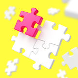 Assembling puzzle pieces on yellow background Stock Images