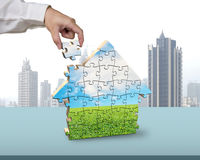 Assembling puzzles in house building shape. In office Stock Images