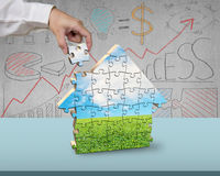 Assembling puzzles in house shape with beautiful landscape. On it Stock Photo