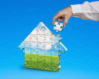 Assembling puzzles in house shape in blue background. Assembling puzzles in house shape isolated in blue background Stock Photography