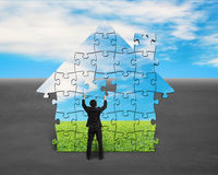 Assembling puzzles in house shape. With blue sky background Royalty Free Stock Image