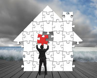 Assembling puzzles in house shape with flood background. Assembling puzzles in house shape with flood and cloudy sky background Stock Images