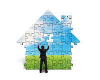 Assembling puzzles for house shape Royalty Free Stock Images