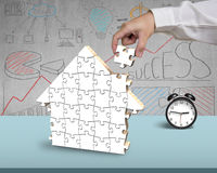 Assembling puzzles for house shape in office. Assembling puzzles for house shape on desk in office Royalty Free Stock Image