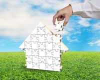 Assembling puzzles in house shape on sod. With blue sky Royalty Free Stock Photos