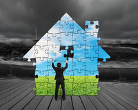 Assembling puzzles in house shape Stock Photo