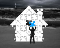 Assembling puzzles in house shape with storm. Background Royalty Free Stock Image