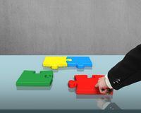 Assembling puzzles on table Stock Photography