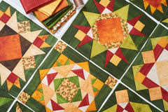 Assembling of quilt from orange-green patchwork blocks, pile of fabric Royalty Free Stock Photos