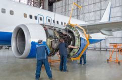Assembling, replacing engine parts of the plane after repair. Specialist mechanic controls the crane of an airplane. Concept maint Royalty Free Stock Photography