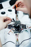 Assembling Spy Drone. Closeup top view shot of male hands unscrewing circuit board of disassembled drone on white table with assorted tools stock photo