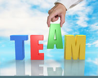 Assembling TEAM 3D word on table with sky reflection Royalty Free Stock Photos