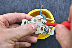 Assembling wall home power socket, close-up. Household electricity supply network, fastening of electric outlet to socket box, hands of electrician close-up royalty free stock photography
