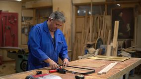 Assembling the wooden frame on the carpentry table in the workshop. With glue and different tools stock footage