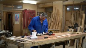 Assembling the wooden frame on the carpentry table in the workshop. With glue and different tools stock video