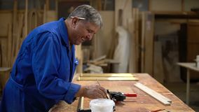 Assembling the wooden frame on the carpentry table in the workshop. With glue and different tools stock video footage