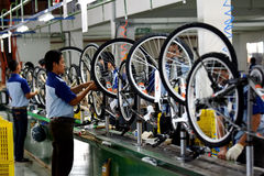 Assembly bicycle bike from Indonesia. SIDOARJO, INDONESIA - APRIL 9, 2015: Workers check on the assembly line at the assembly bicycle bike from Indonesia Polygon Stock Images