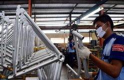 Assembly bicycle bike from Indonesia. SIDOARJO, INDONESIA - APRIL 9, 2015: Workers check on the assembly line at the assembly bicycle bike from Indonesia Polygon Stock Photo