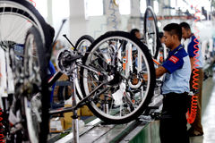 Assembly bicycle bike from Indonesia. SIDOARJO, INDONESIA - APRIL 9, 2015: Workers check on the assembly line at the assembly bicycle bike from Indonesia Polygon royalty free stock photography