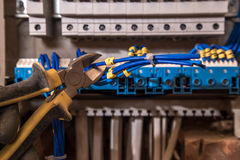 The Assembly of the electrical panel, electrician job, a robot with wires and circuit breakers Royalty Free Stock Images